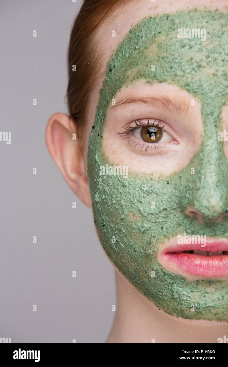 Cropped image of young woman wearing face mask - Stock Image