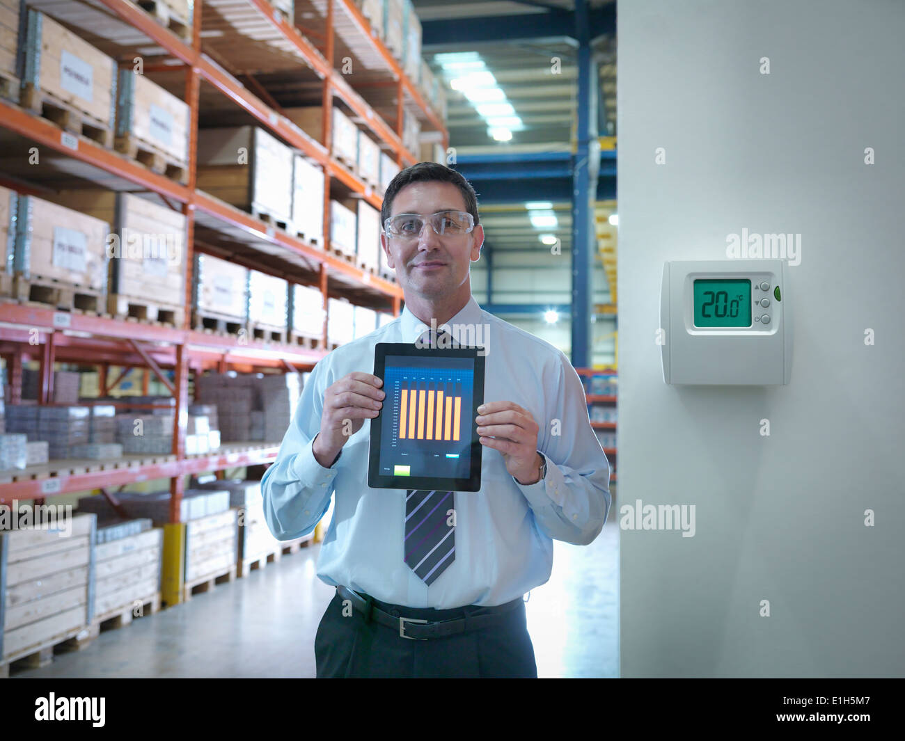 Portrait of proud office worker showing energy saving on digital tablet in factory - Stock Image