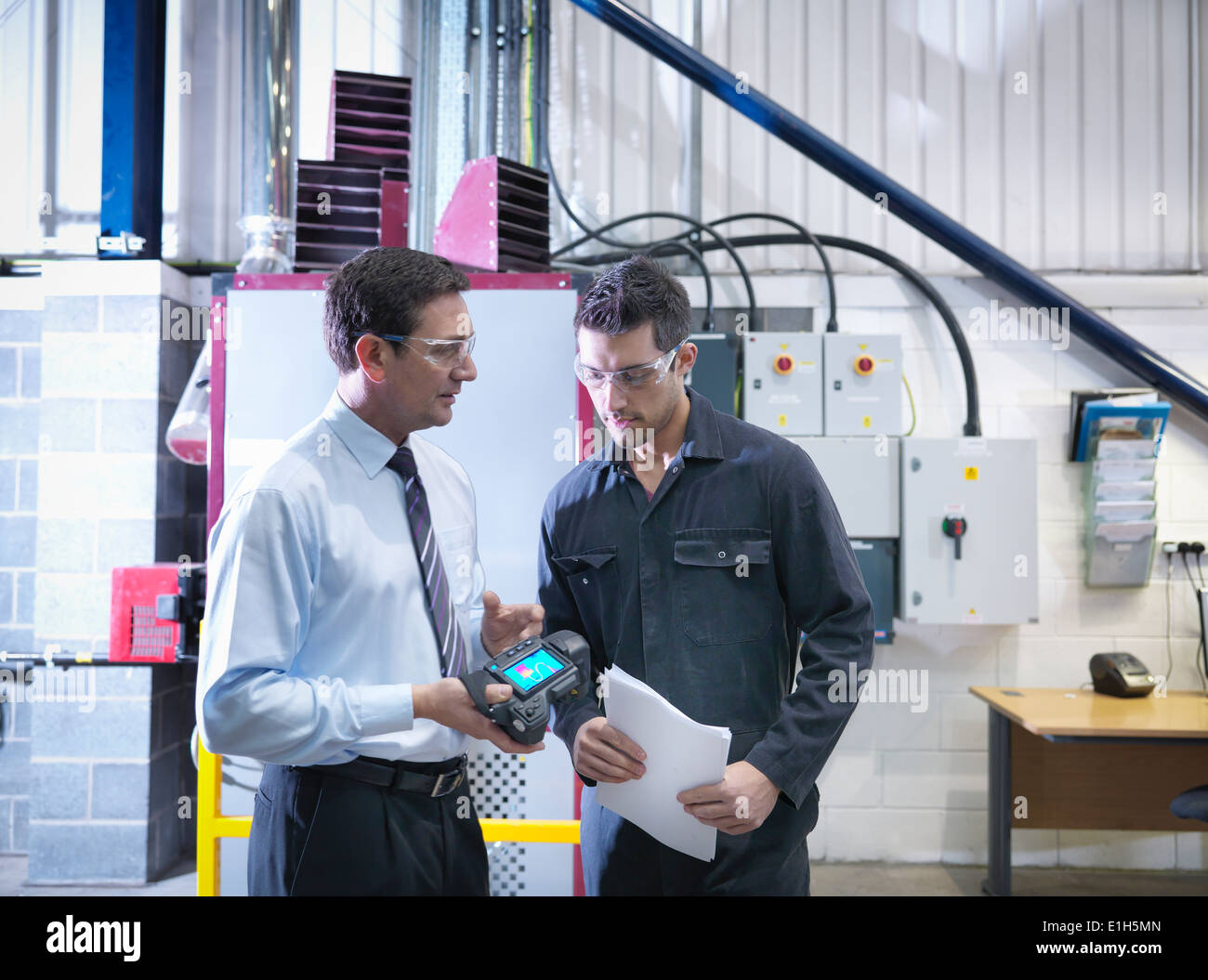 Office manager and worker discuss energy use with infra red camera next to boiler in factory - Stock Image