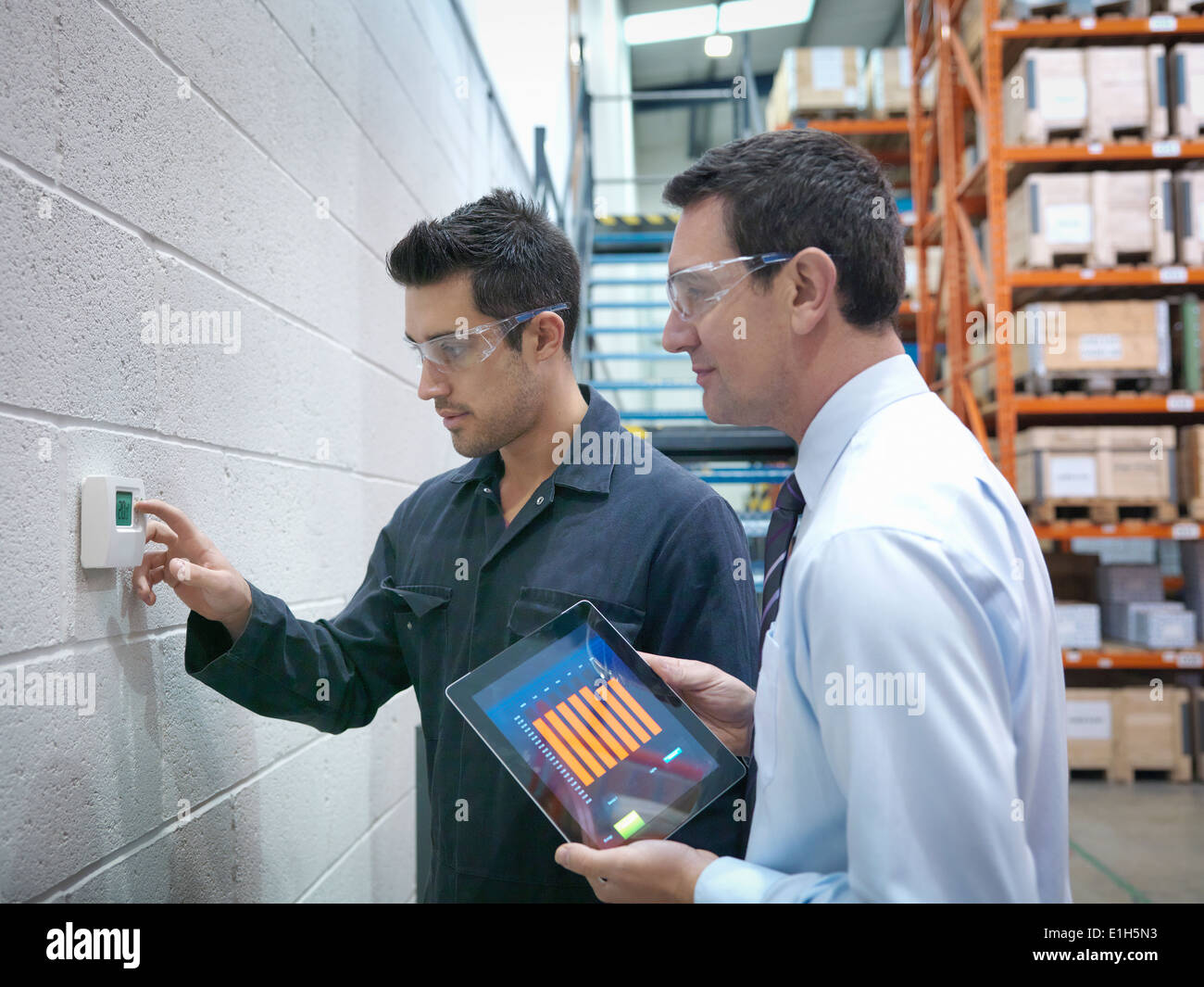 Factory and office workers checking thermostat in factory - Stock Image