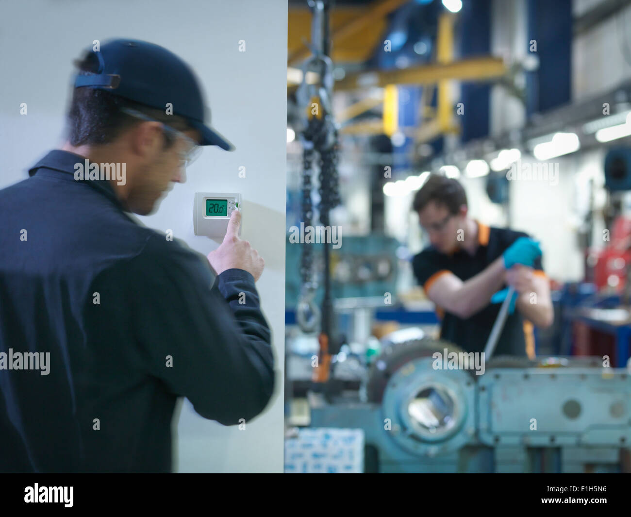 Worker adjusting thermostat in factory - Stock Image
