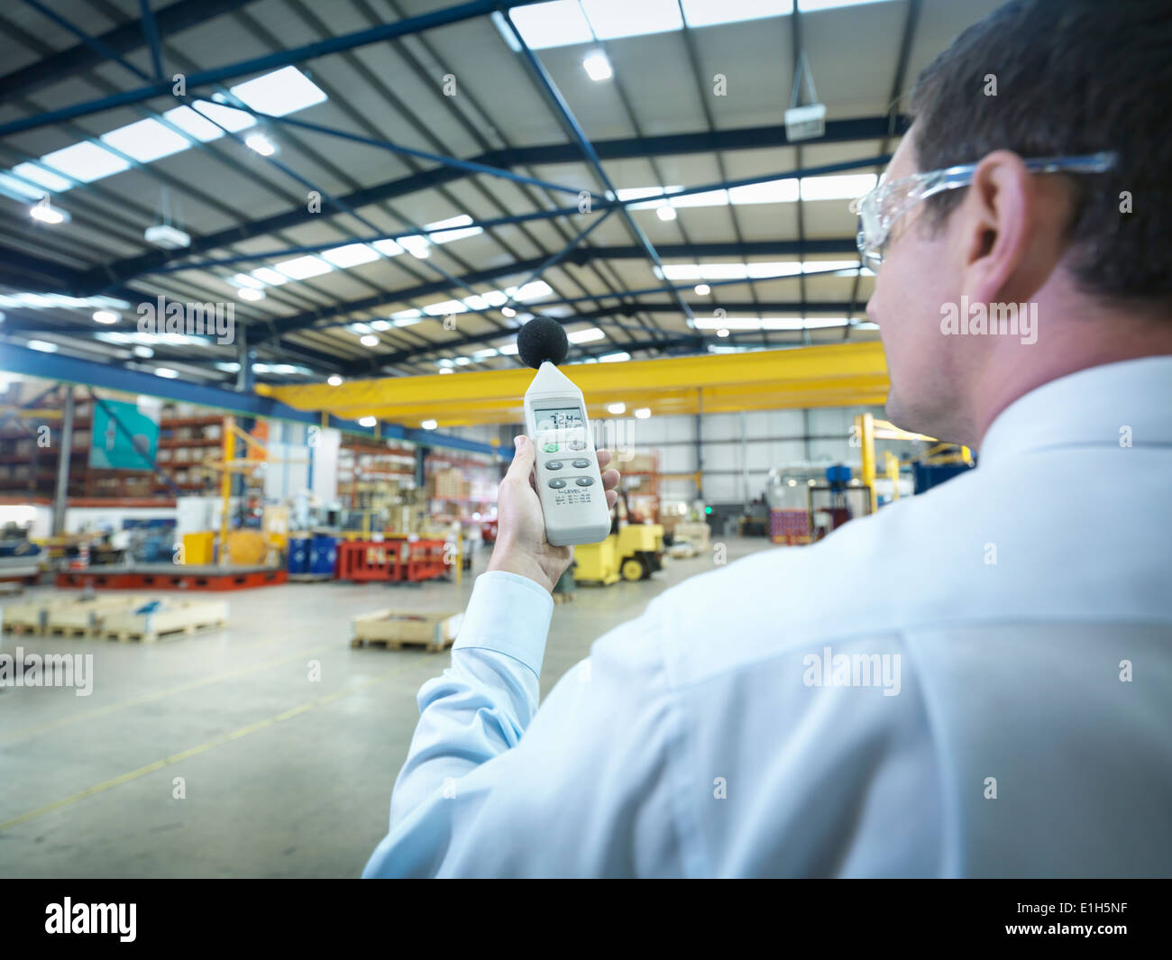 Office worker checking sound volume in factory - Stock Image
