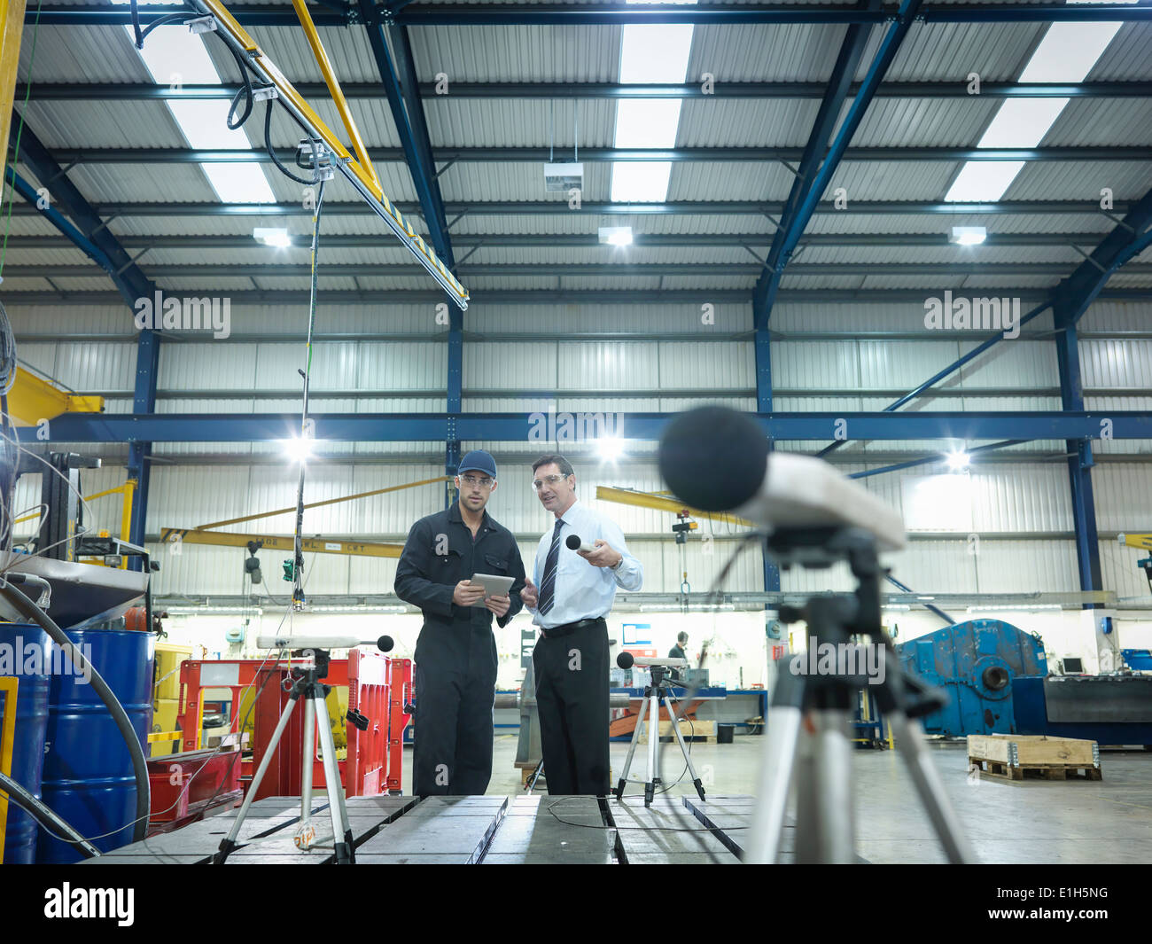 Office and factory worker checking sound volume in factory Stock Photo
