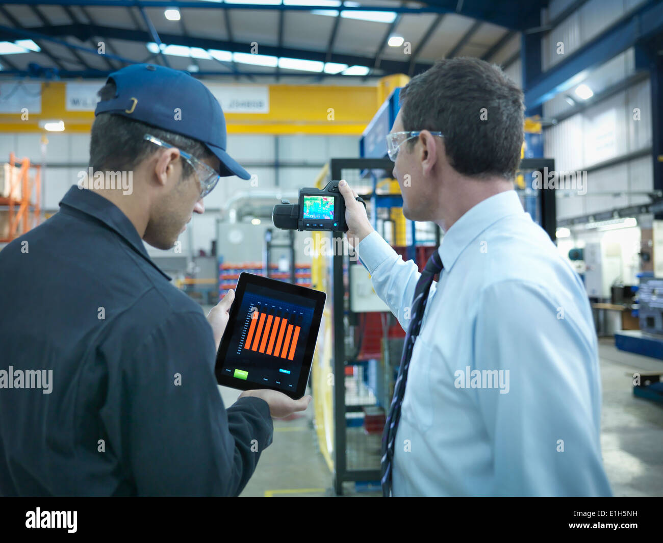 Office and factory worker using digital tablet and infra red camera to check power use in factory - Stock Image