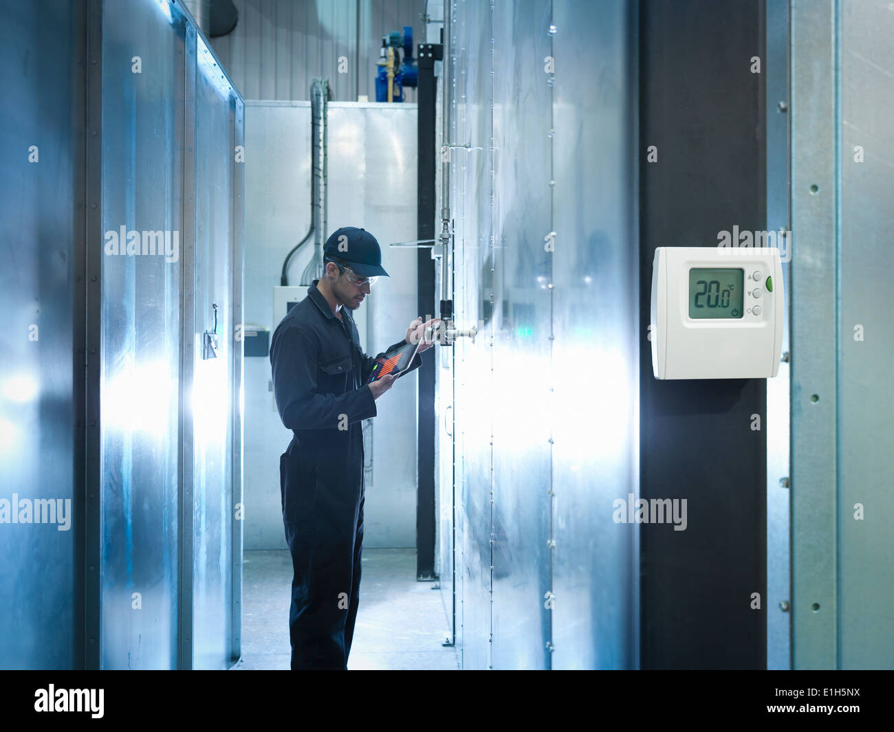 Factory worker using digital tablet to check power use in factory - Stock Image