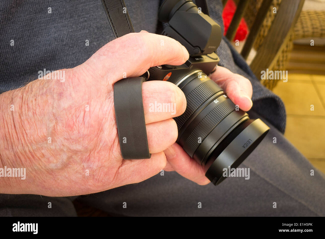 Demonstration of use of Leica Finger Loop attached to camera hand-grip for added security - Stock Image