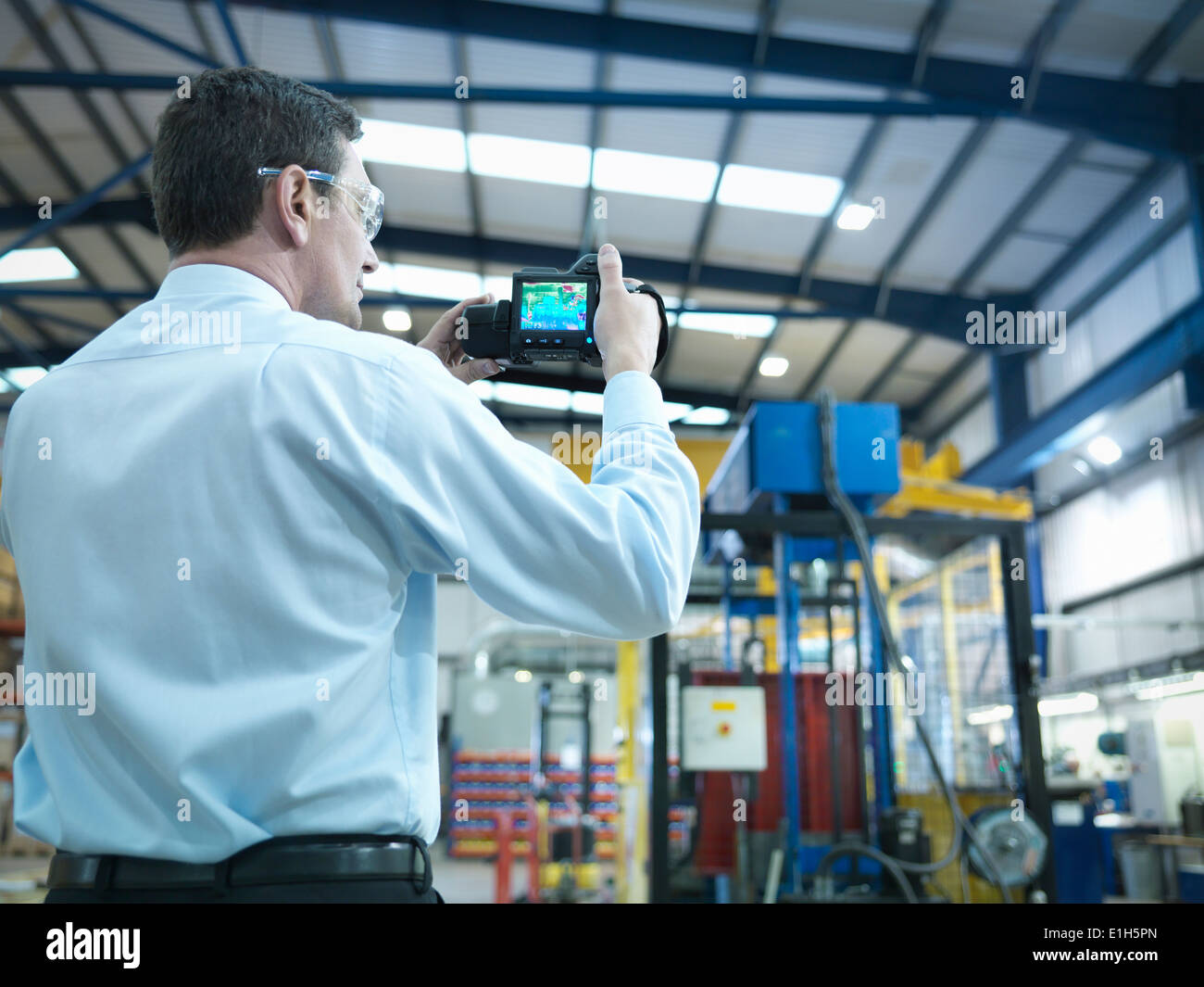 Office worker using infra red camera to check power use in factory - Stock Image