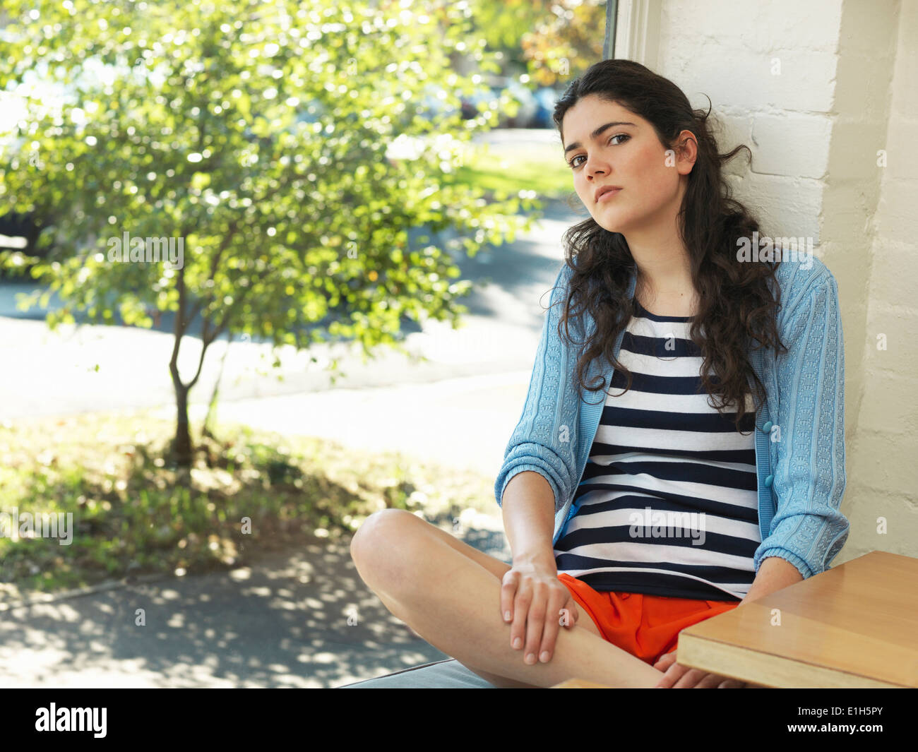 Portrait of sullen young woman leaning against wall - Stock Image