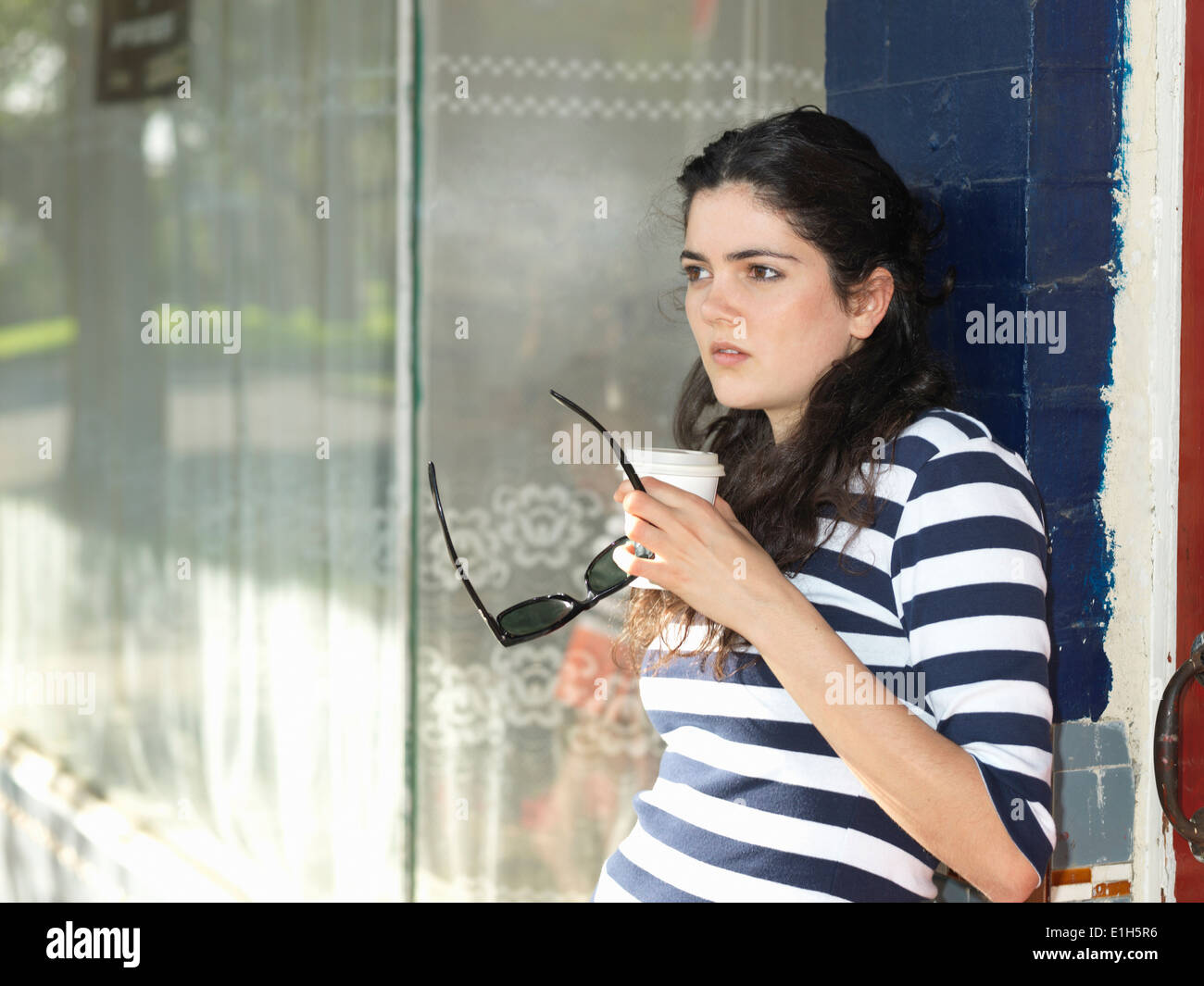 Young woman with takeaway coffee waiting outside cafe - Stock Image