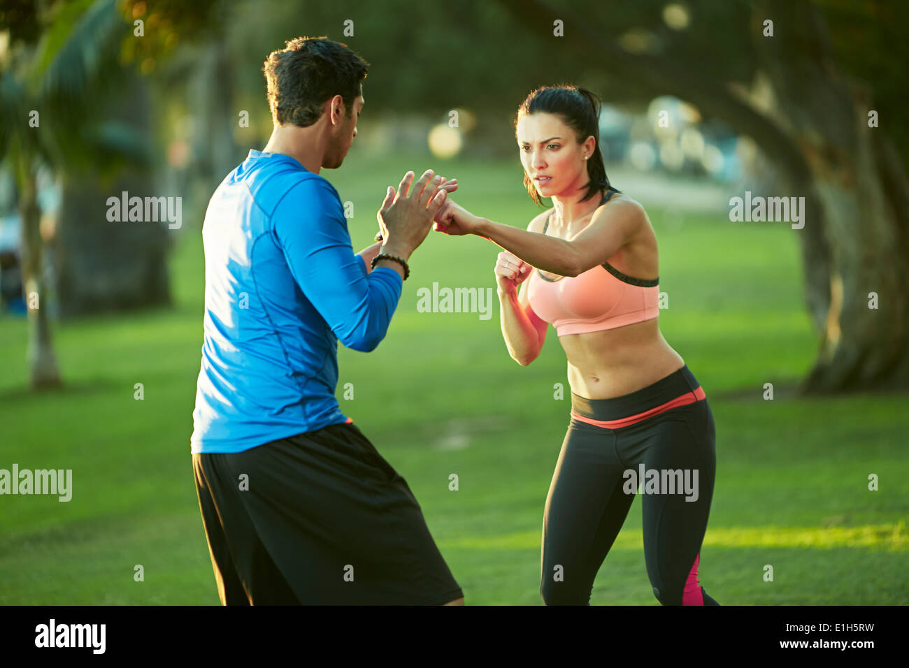 Man and woman in park boxing - Stock Image