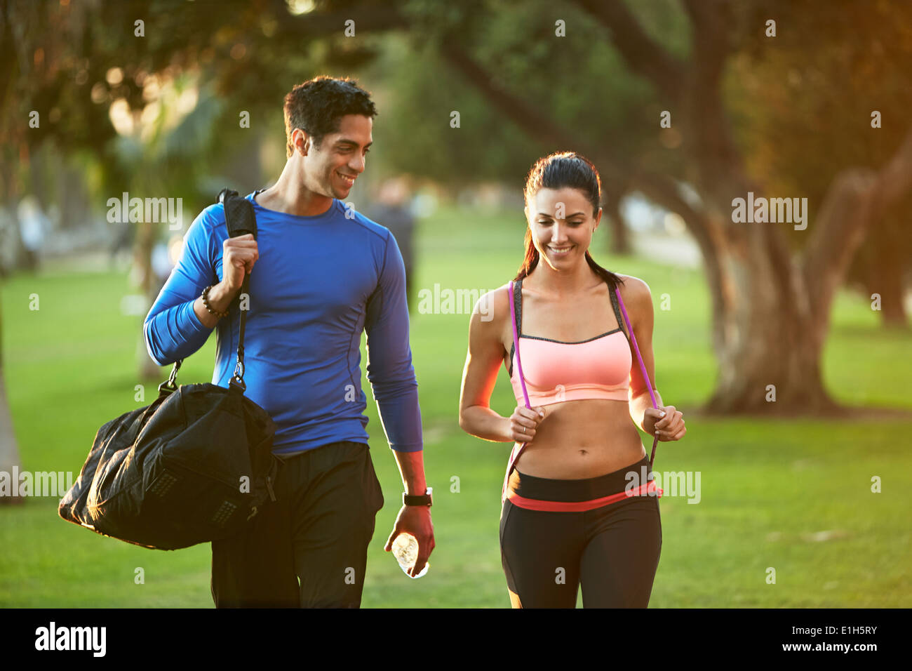 Man and woman wearing sports clothes walking through park - Stock Image