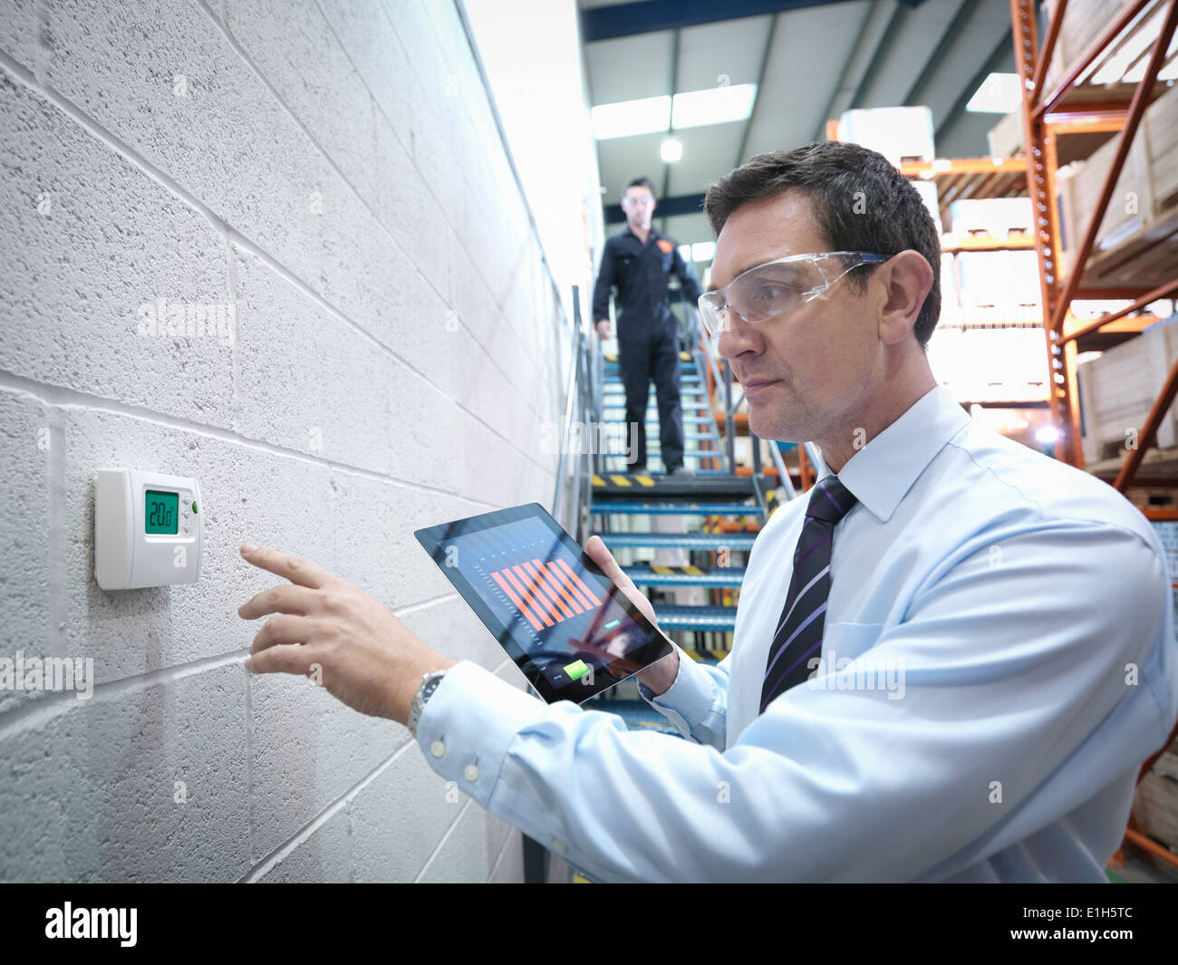 Office worker checking thermostat in factory - Stock Image