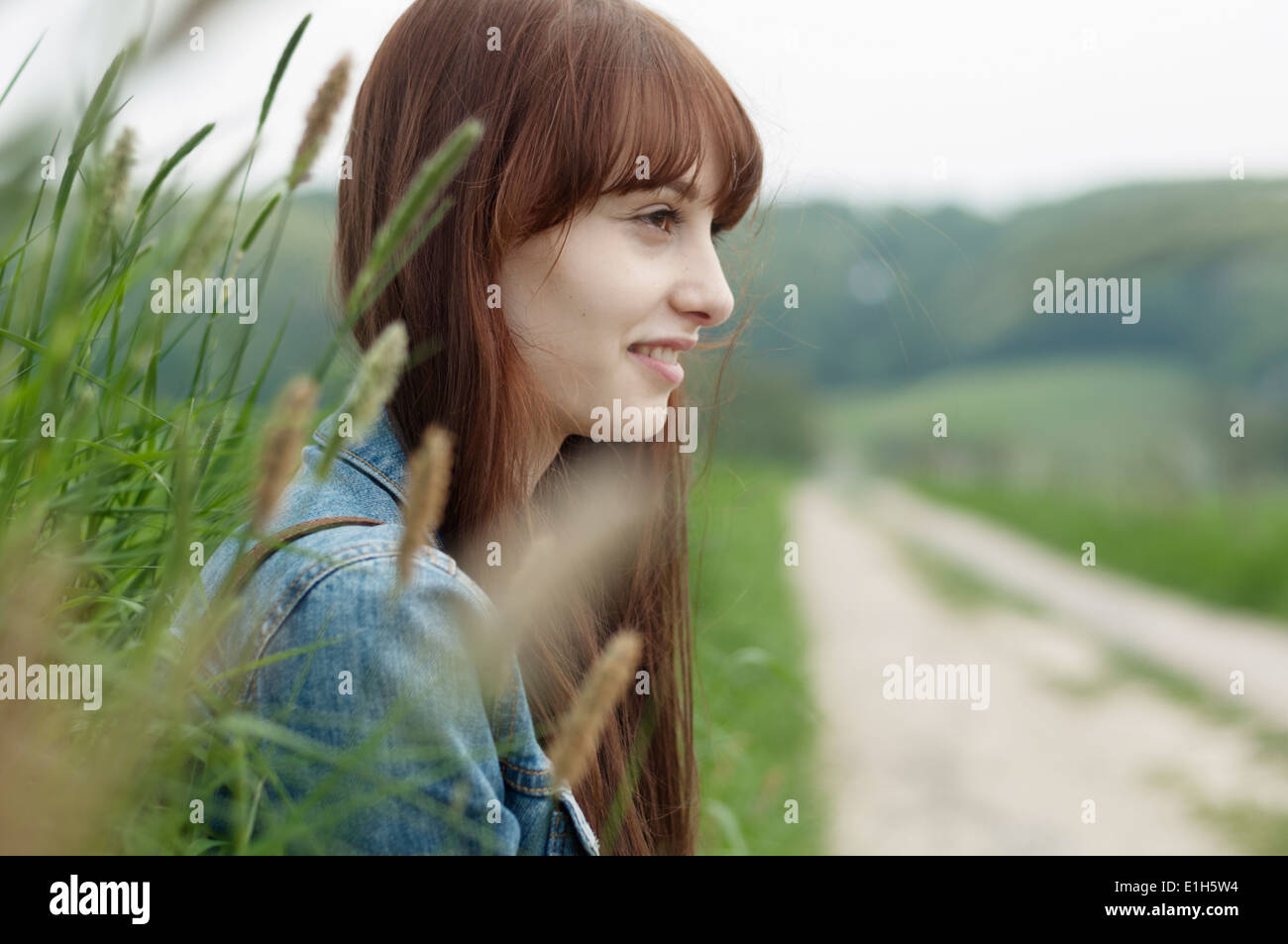 Portrait of young woman next to dirt track - Stock Image