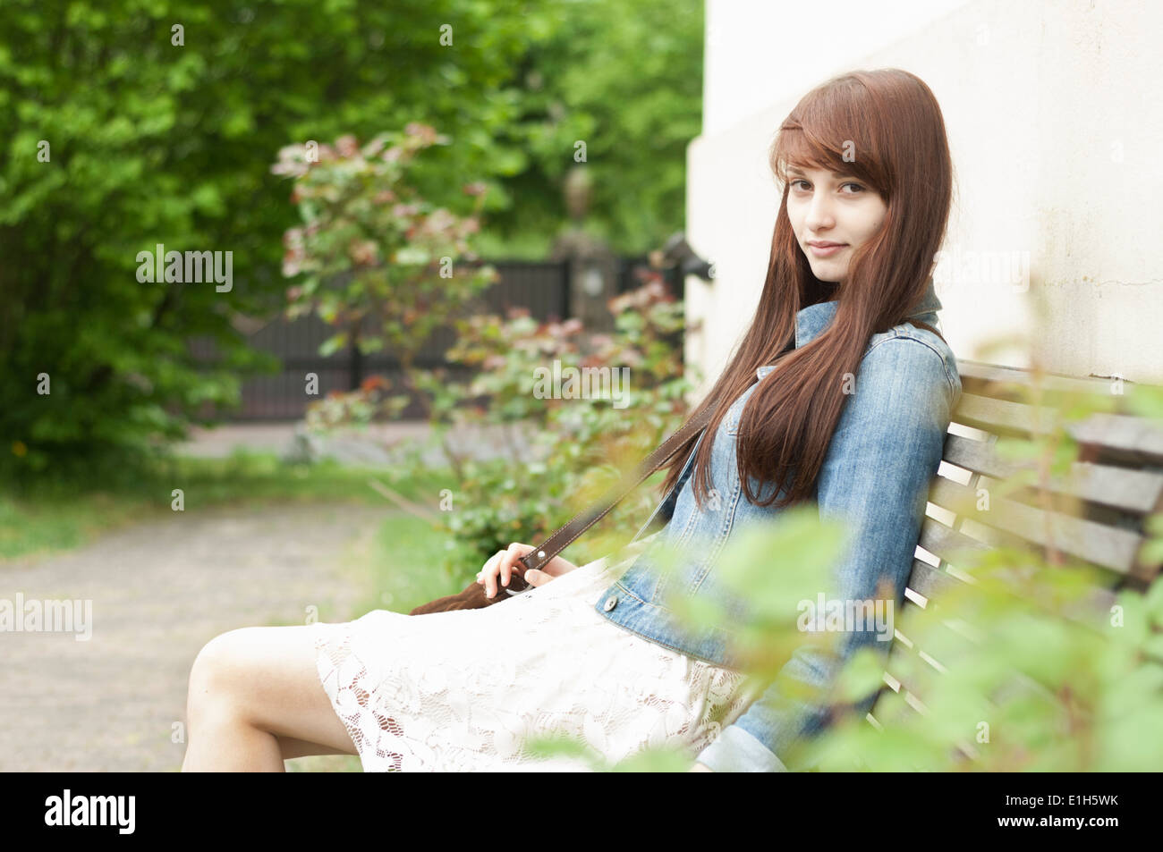 Portrait of young woman sitting on garden bench Stock Photo
