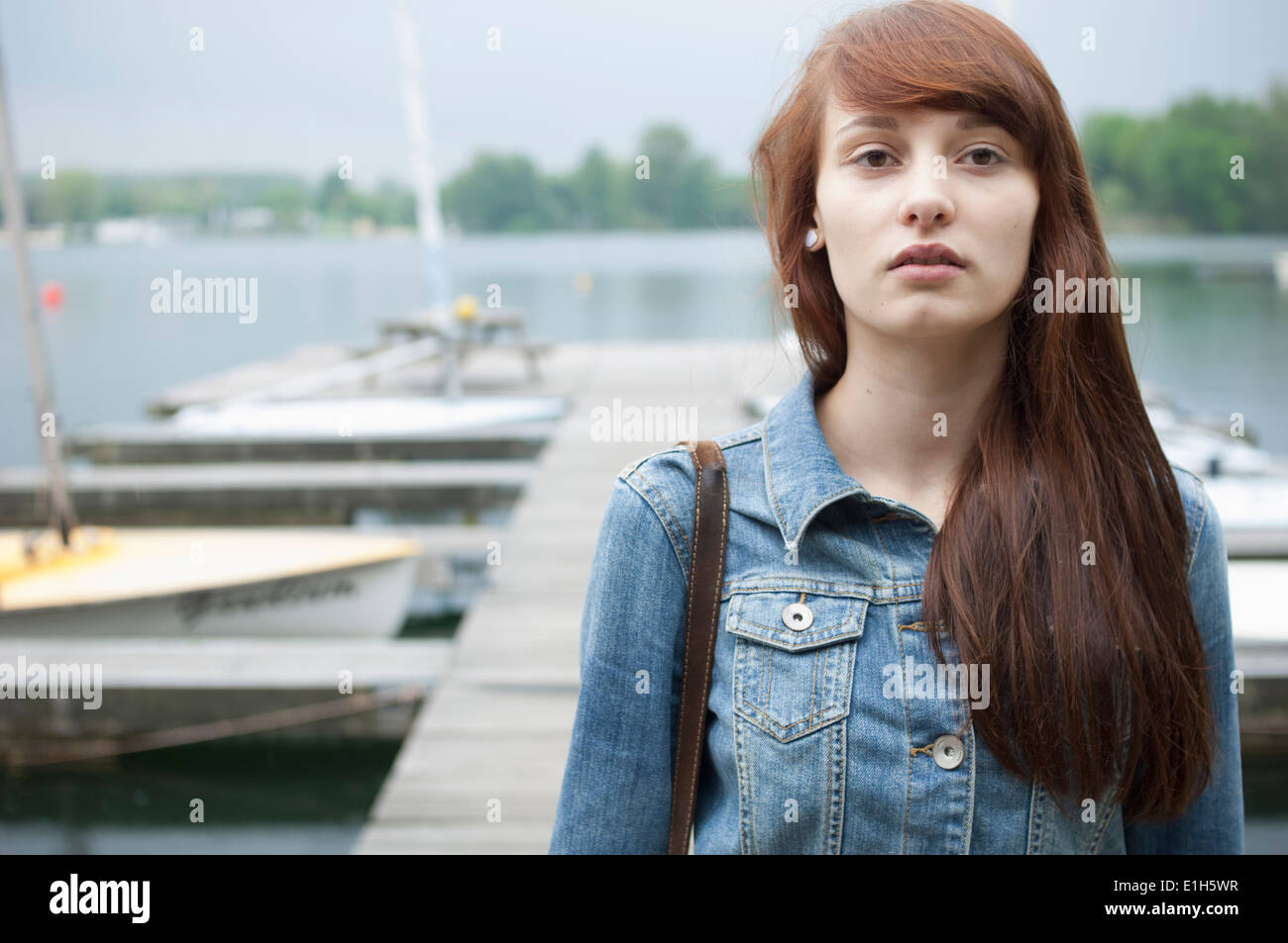 Portrait of serious young woman by lake - Stock Image