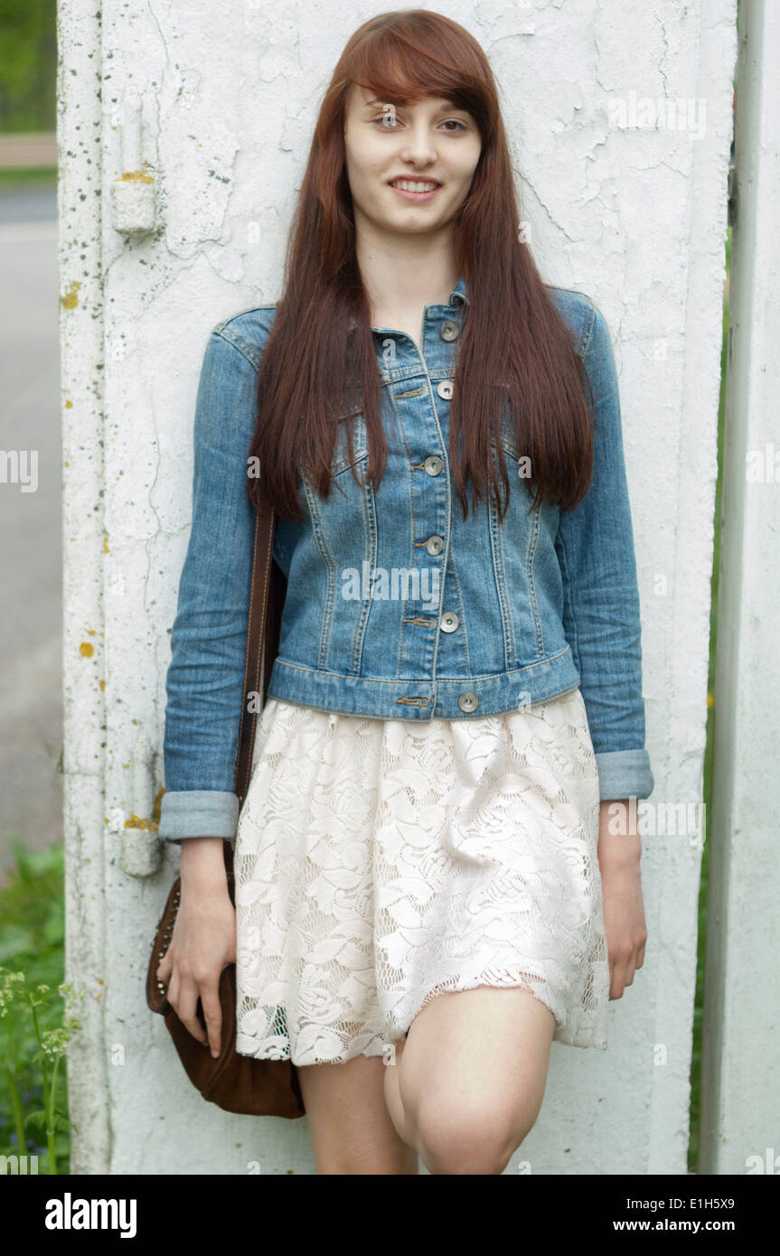 Portrait of young woman leaning against wall Stock Photo