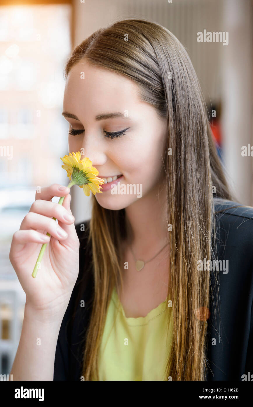 Portrait of young woman in cafe smelling flower Stock Photo