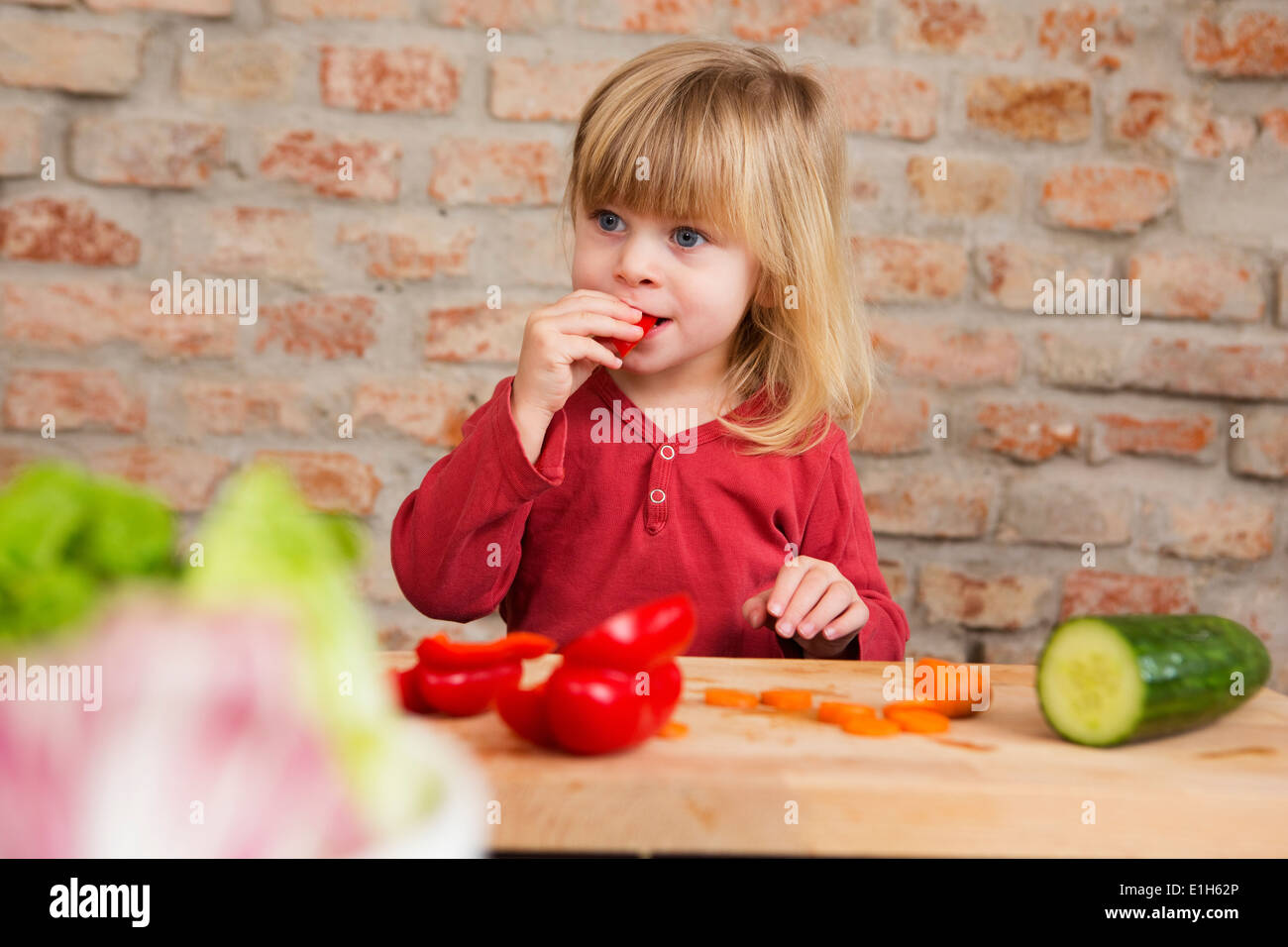 Two year old girl in kitchen eating raw vegetables - Stock Image