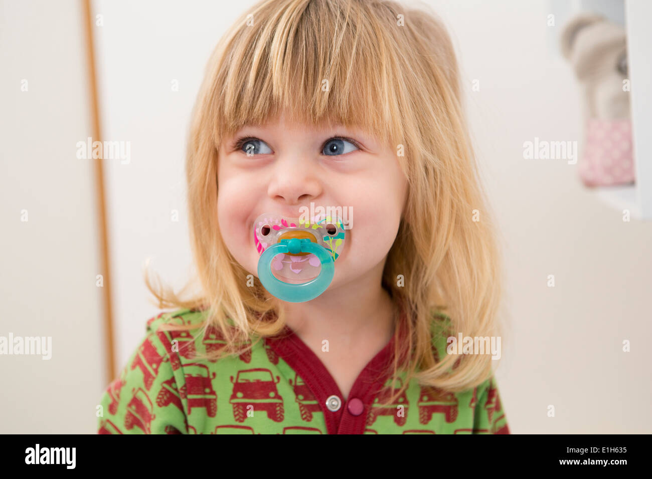 Portrait of happy 2 year old girl with pacifier - Stock Image