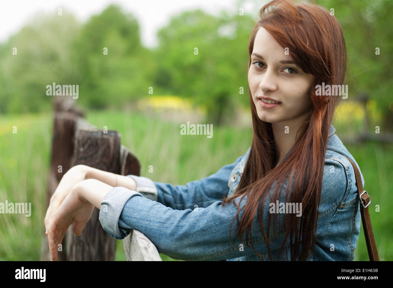 Portrait of young woman leaning on rustic fence - Stock Image