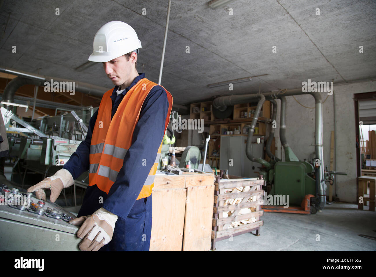 Young male woodworker operating machine control panel - Stock Image