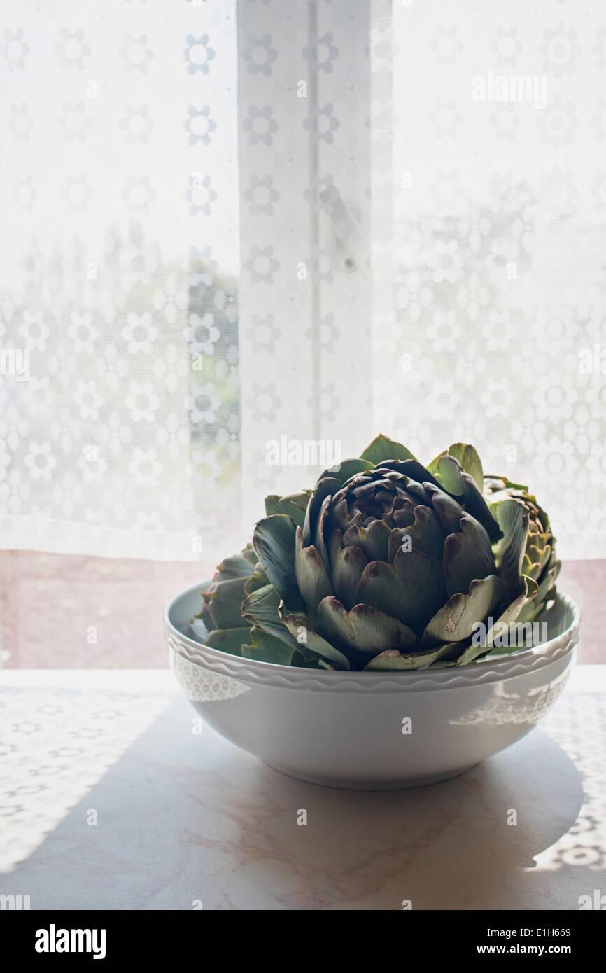 Artichoke in a bowl on sunlit windowsill - Stock Image