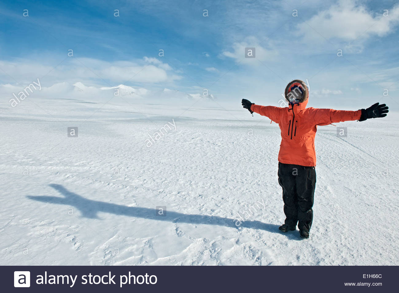 Young female hiker with arms outstretched in snowy covered landscape, Skaftafell, Vatnajokull National Park, Iceland - Stock Image