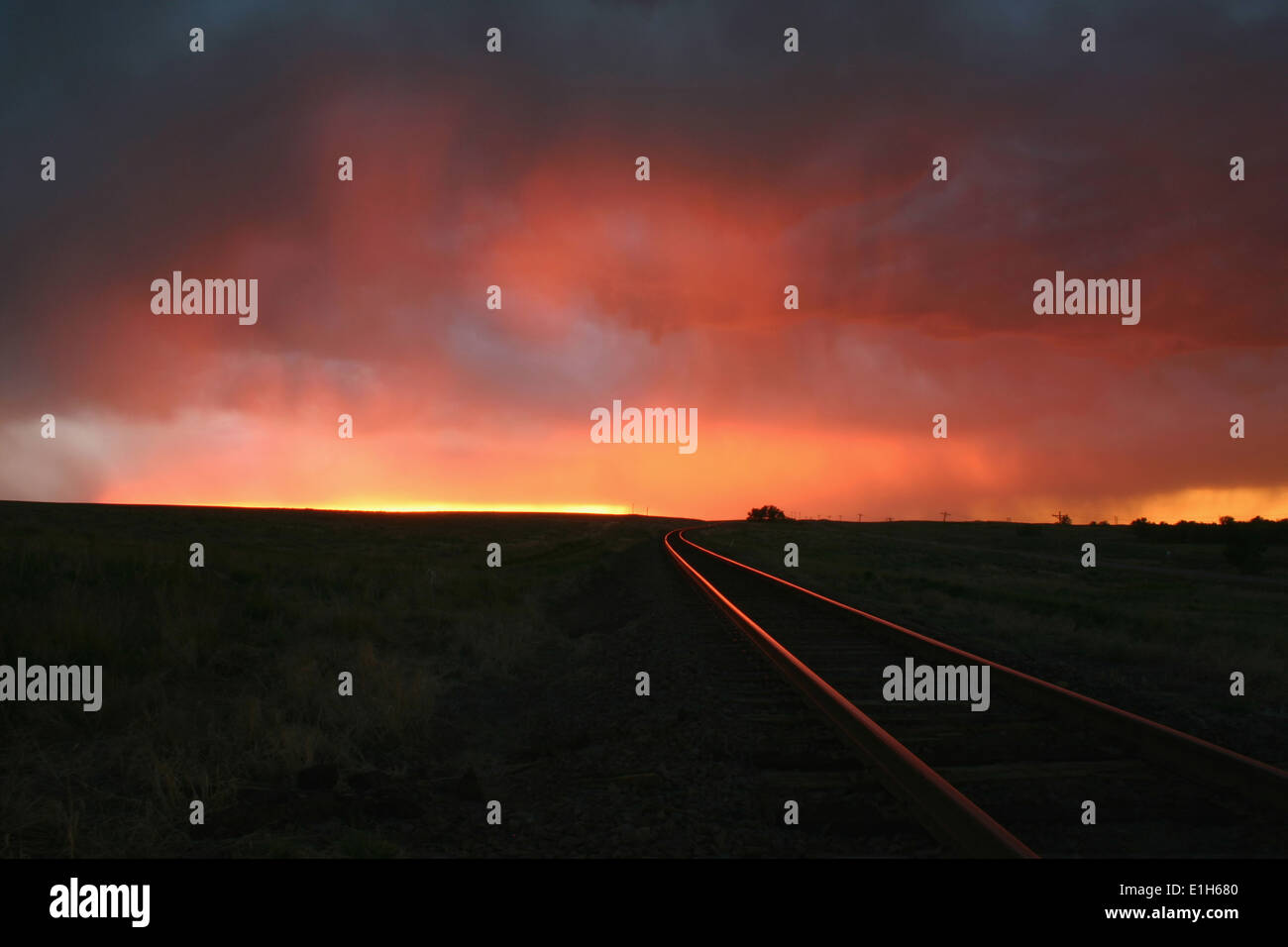 Intense sunset colors illuminate the railroad tracks over this remote location, Burlington, Colorado, USA Stock Photo