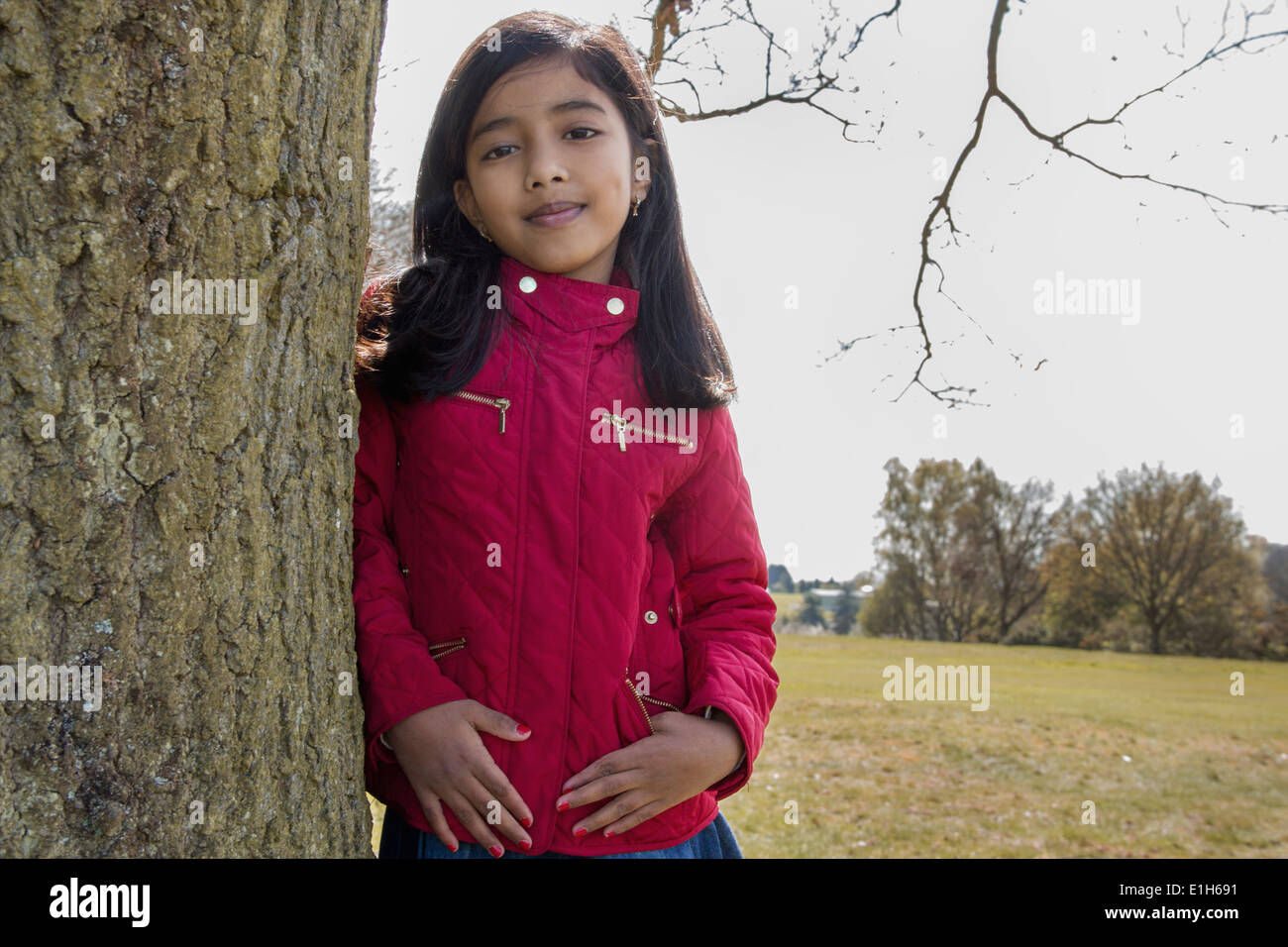 Portrait of girl leaning against tree trunk - Stock Image