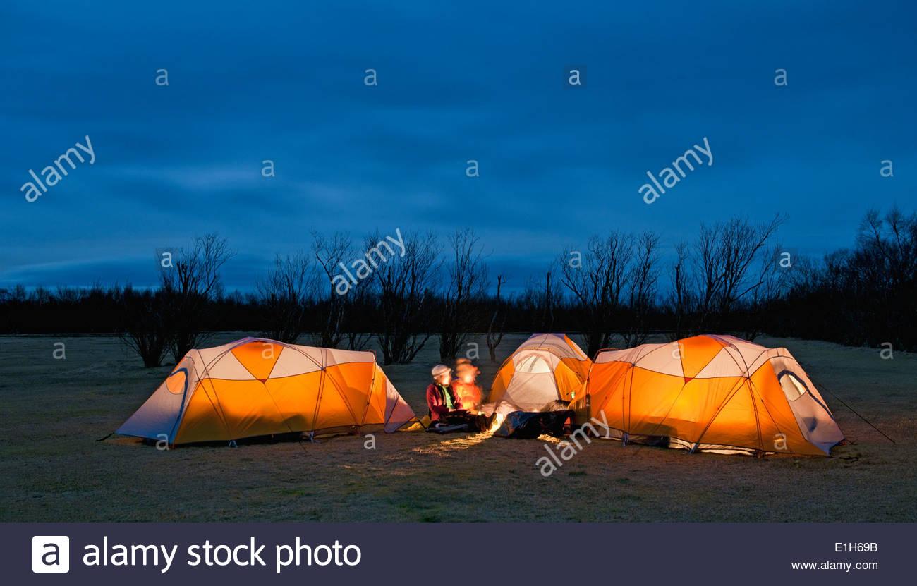 Three friends chatting outside tents at night, Skaftafell, Vatnajokull National park, Iceland - Stock Image