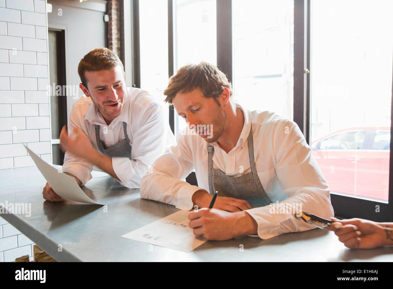 Chefs preparing for service in restaurant - Stock Image