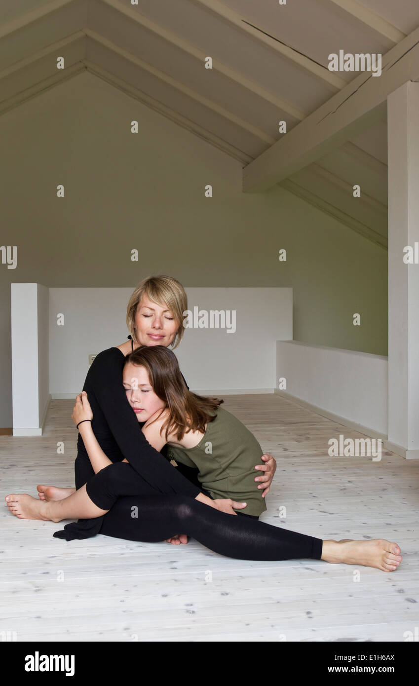 Mother and twelve year old daughter hugging on floor - Stock Image