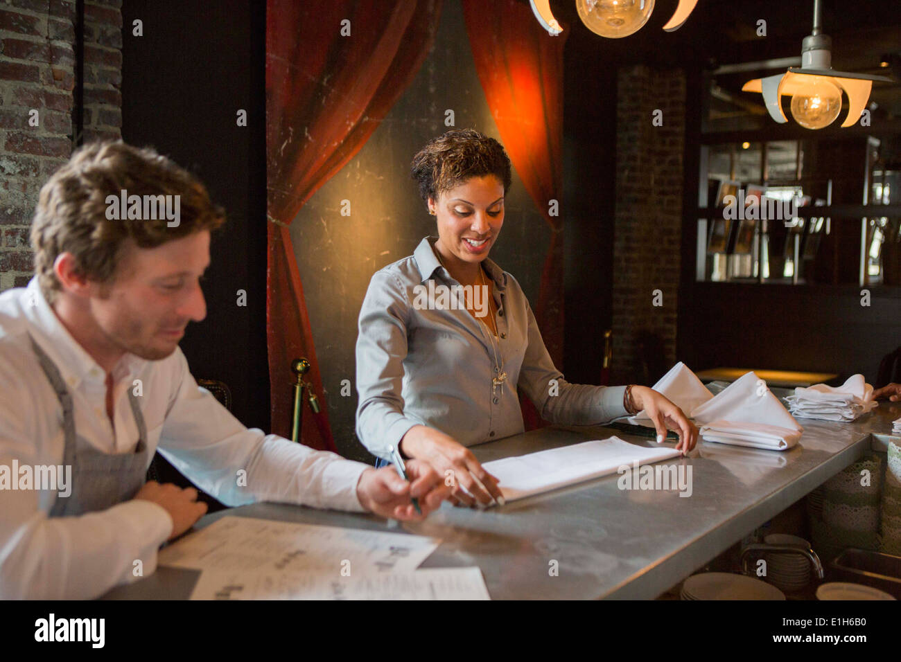 Chef and waitress preparing for service in restaurant - Stock Image