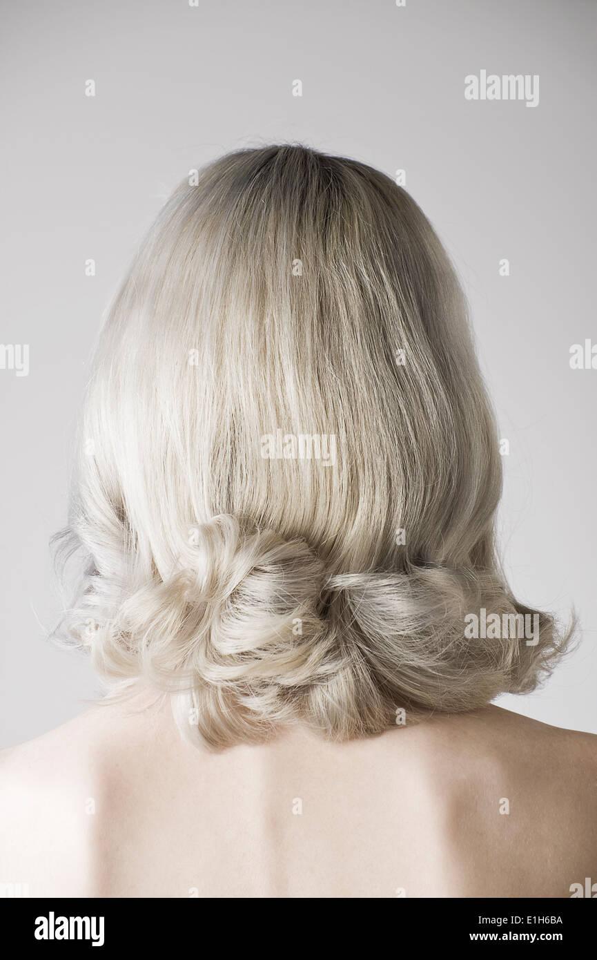 Studio portrait of mature woman rear view - Stock Image
