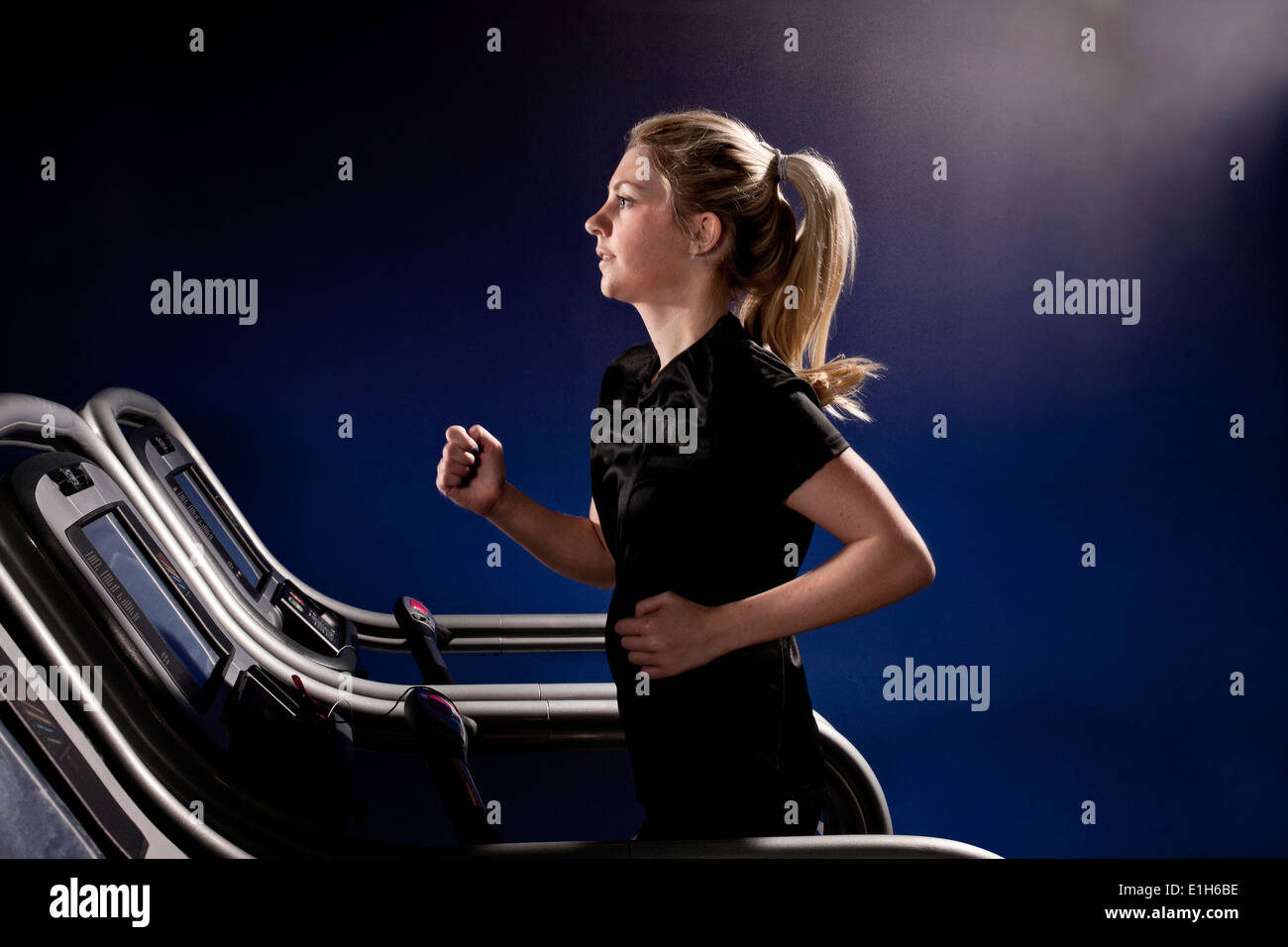 Young woman running on treadmill at gym in altitude centre - Stock Image