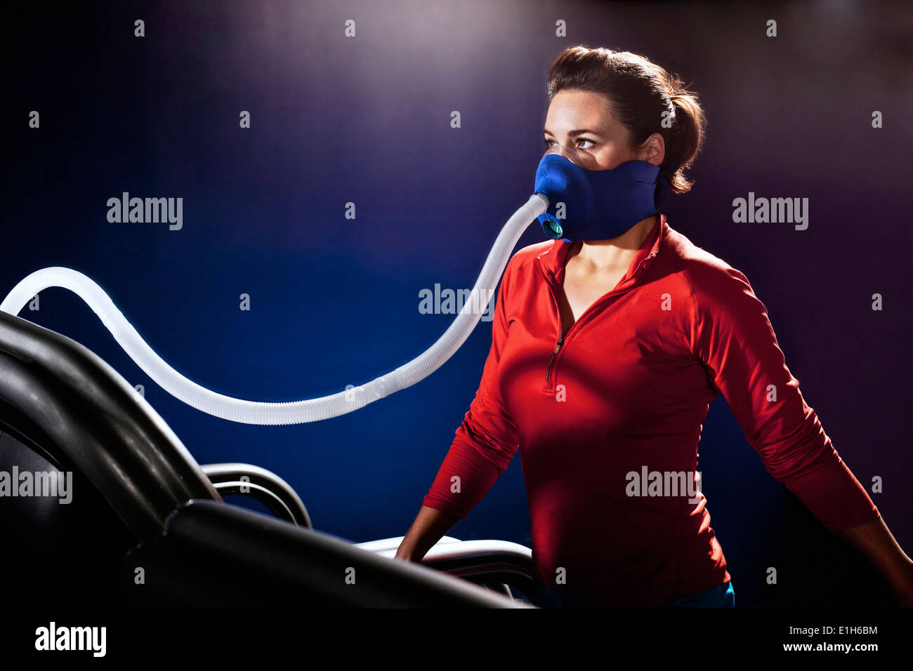 Mid adult woman with face mask on gym treadmill in altitude centre - Stock Image