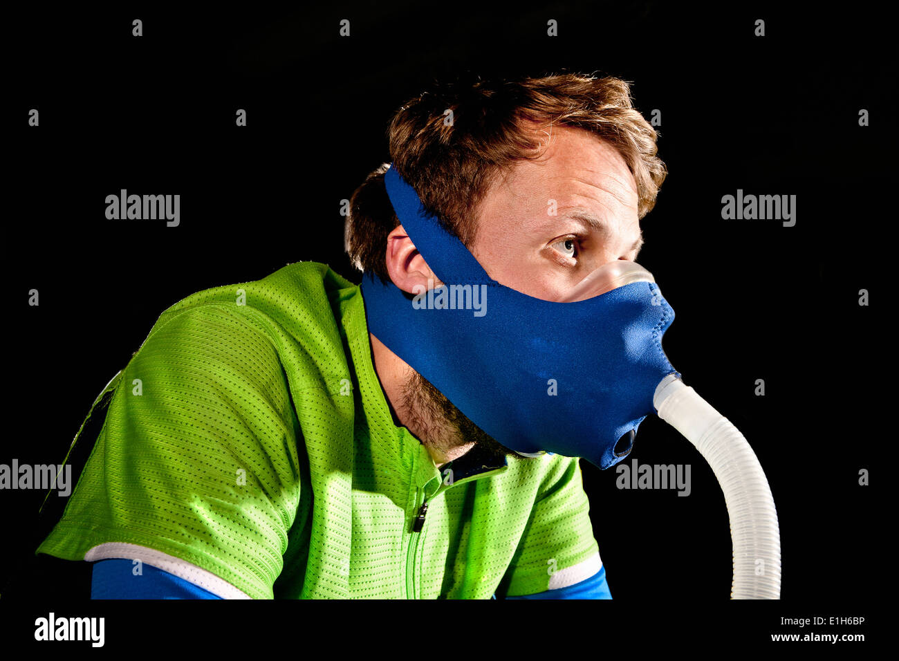 Close up of young man in face mask on gym exercise cycle in altitude centre - Stock Image
