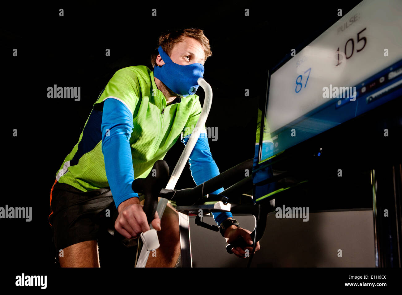 Young man in face mask on gym exercise cycle in altitude centre - Stock Image