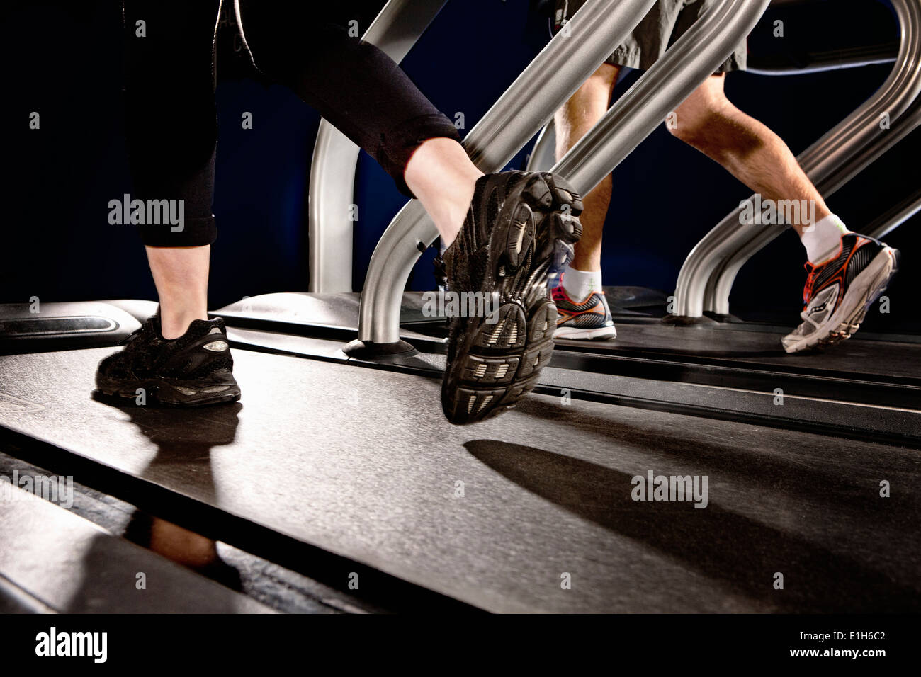 Close up of male and female legs running on gym treadmill in altitude centre - Stock Image