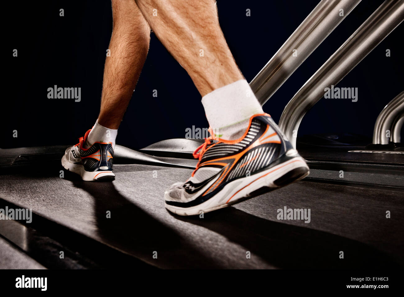 Close up of male legs running on gym treadmill in altitude centre - Stock Image