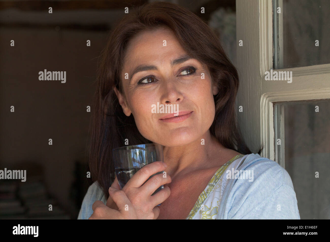 Portrait of mature adult woman with drinking glass - Stock Image
