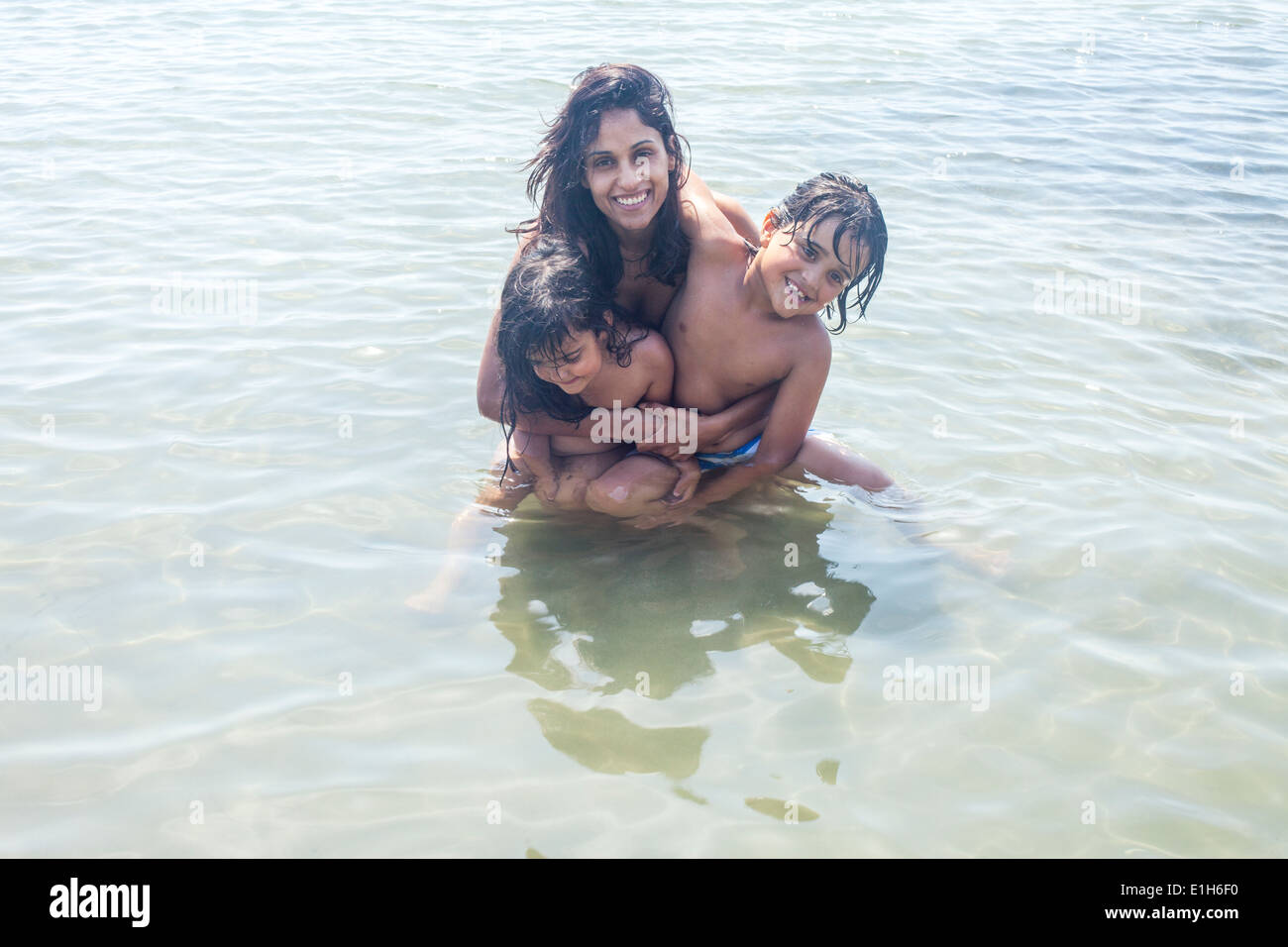 Portrait of mother and two children in sea - Stock Image