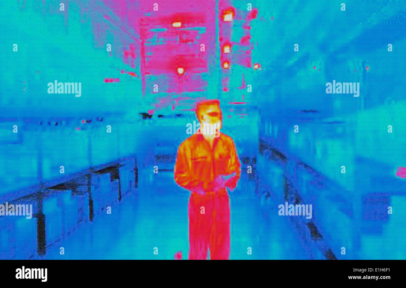 Infra red heat image of warehouse worker in factory - Stock Image