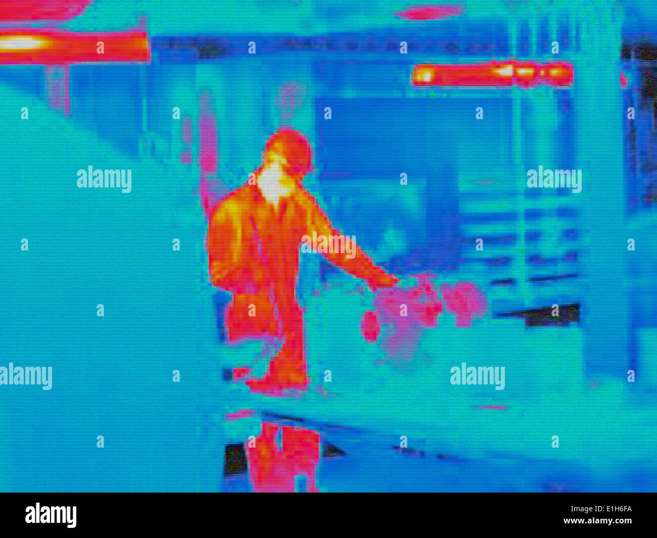 Infra red heat image of worker in factory - Stock Image