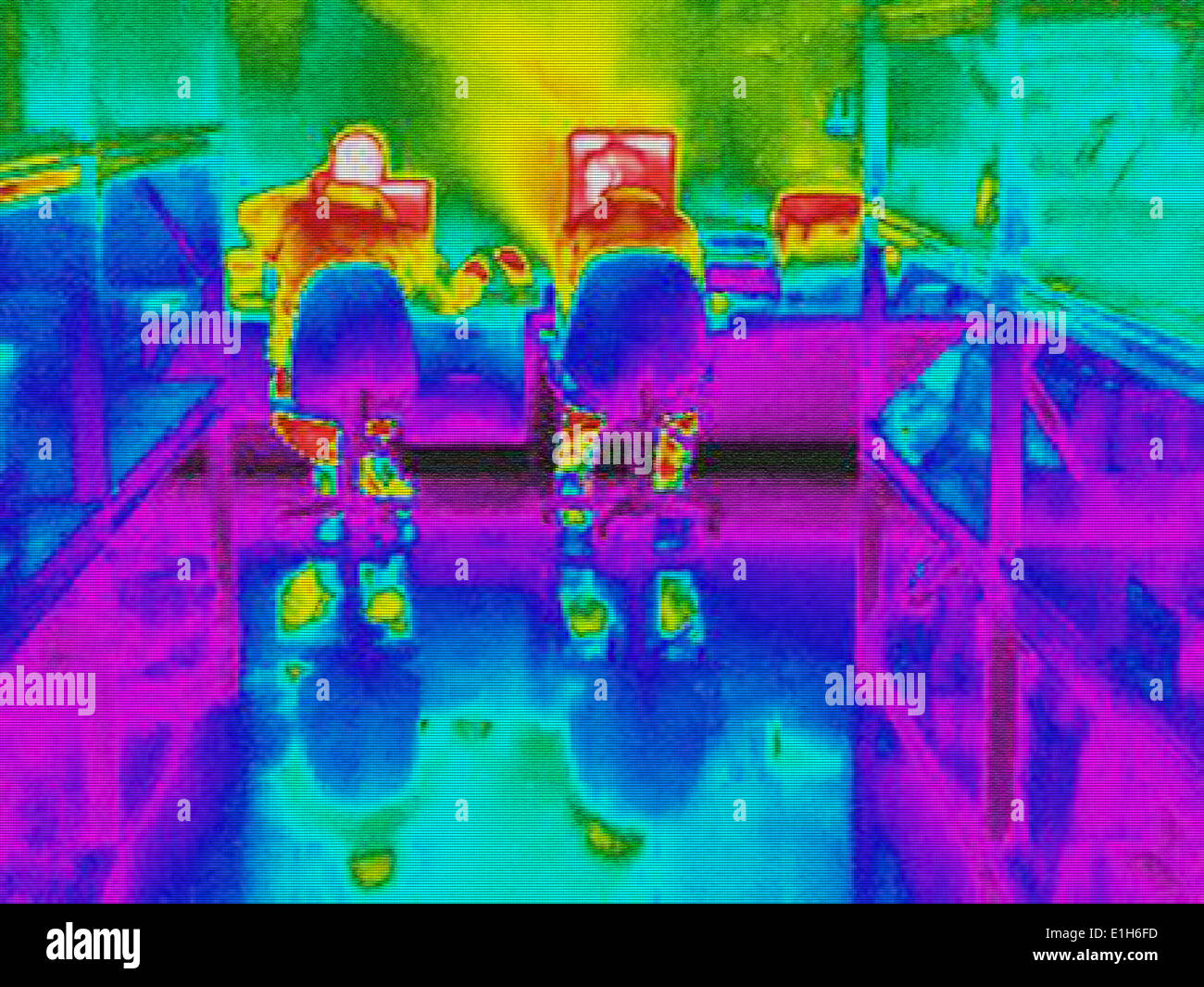 Infra red heat image of workers and heat loss at computer work station - Stock Image