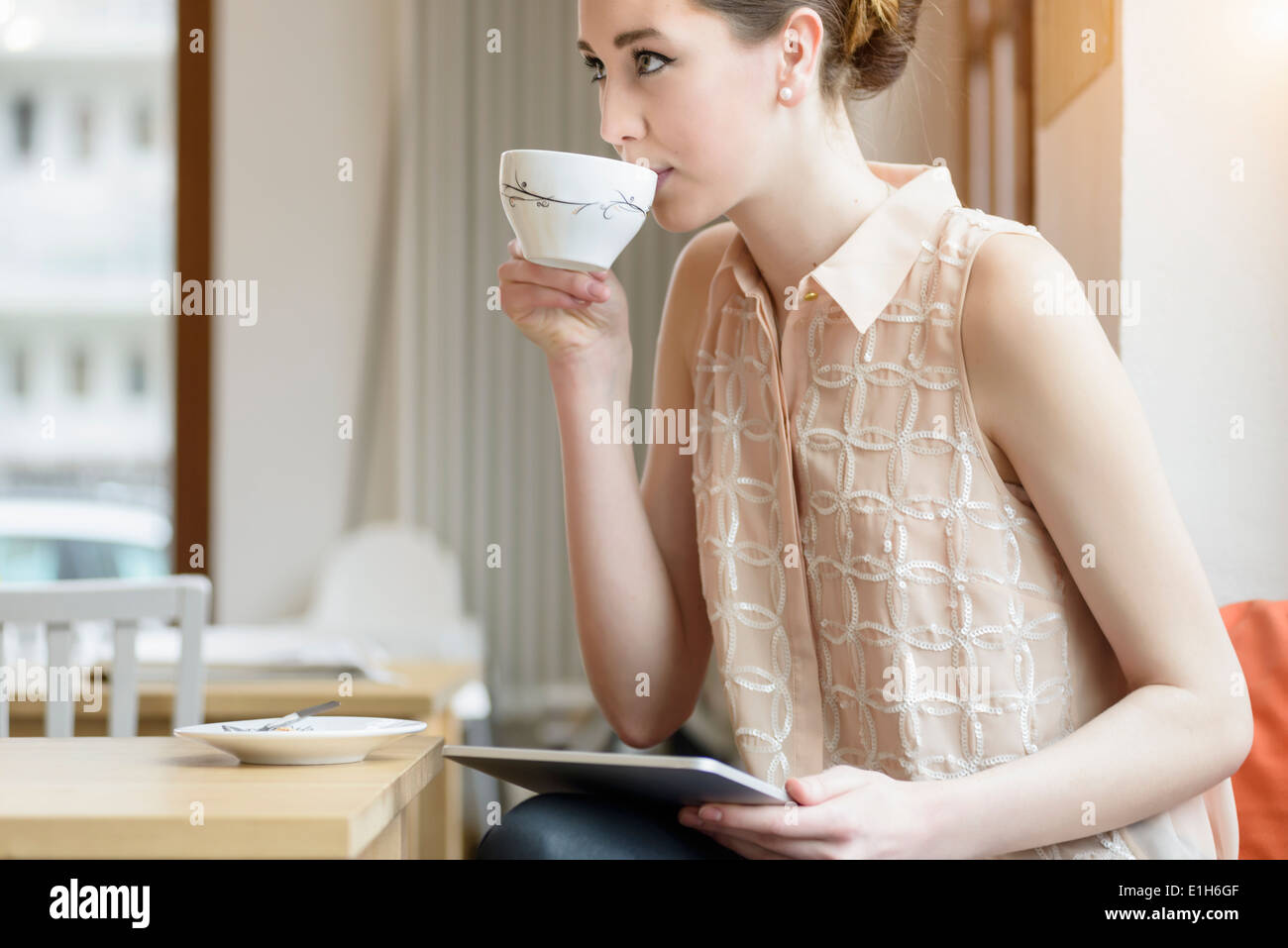 Young businesswoman in cafe drinking coffee and using digital tablet - Stock Image