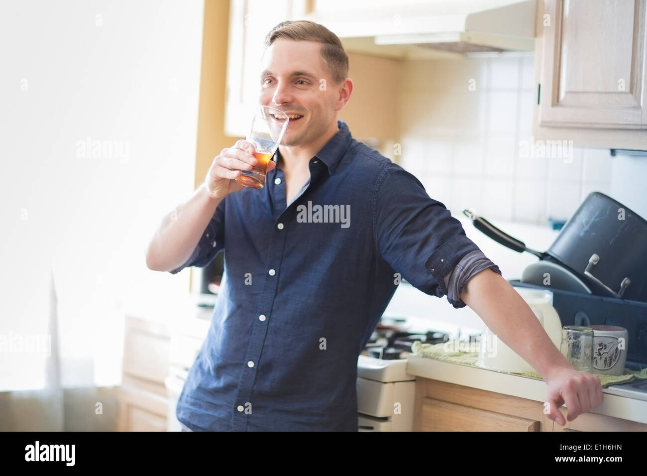 Mid adult man checking taste of home brew beer in glass - Stock Image