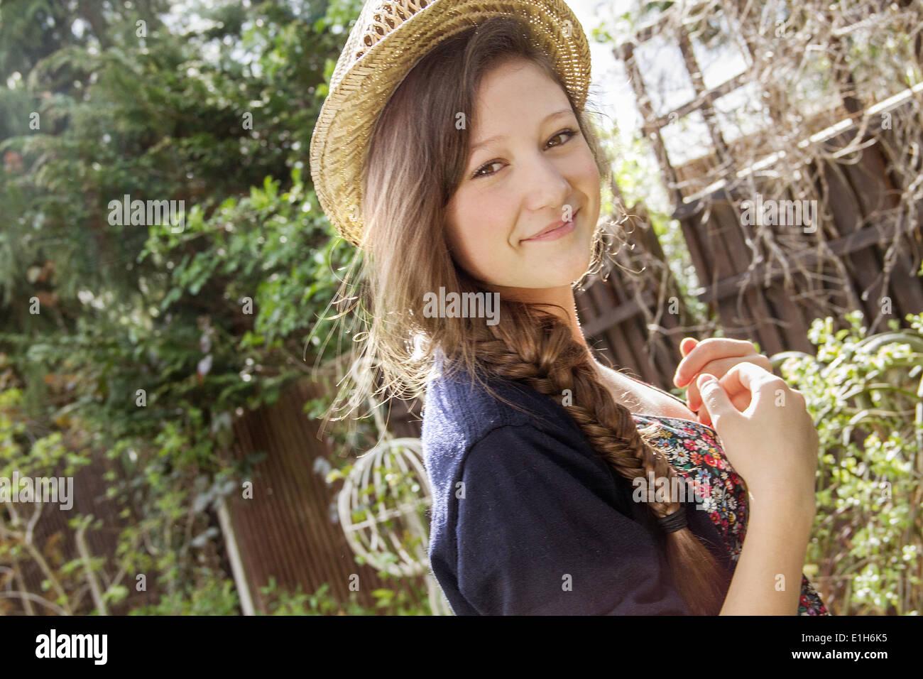 Portrait of teenage girl in straw hat in garden - Stock Image