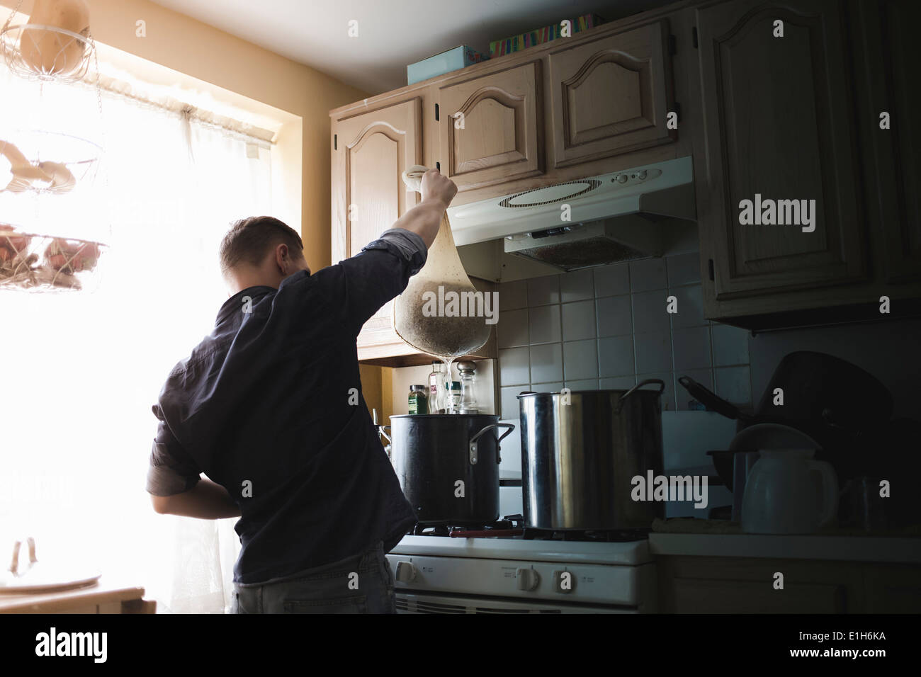 Mid adult man holding up seeping bag for home brew beer - Stock Image