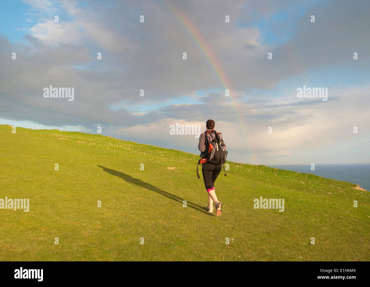 Young female hiker, hiking up hill toward rainbow - Stock Image
